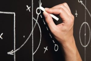 Hand_drawing_a_soccer_game_tactics_with_white_chalk_on_blackboard.