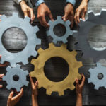 Group_of_business_people_joining_together_silver_and_golden_colored_gears_on_table_at_workplace_top_view