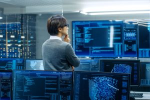 In_the_System_Control_Room_Technical_Operator_Stands_and_Monitors_Various_Activities_Showing_on_Multiple_Displays_with_Graphics._Administrator_Monitors_Work_of__Artificial_Intelligence,_Big_Data_Mining,_Neural_Network,_Surveillance_Project.