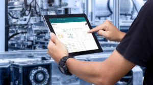 Hands_holding_tablet_on_blurred_automation_machine_as_background