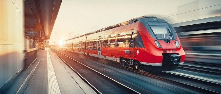 Beautiful_railway_station_with_modern_high_speed_red_commuter_train_with_motion_blur_effect_at_colorful_sunset_in_Nuremberg,_Germany._Railroad_with_vintage_toning