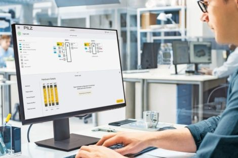 Over_the_Shoulder_Shot_of_Engineer_Working_with_CAD_Software_on_Desktop_Computer,_Screen_Shows_Technical_Drafts_and_Drawings._In_the_Background_Engineering_Facility_Specialising_on_Industrial_Design