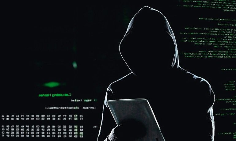 Cyber_attack_with_unrecognizable_hooded_hacker_using_tablet_computer,_cybercrime