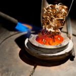pieces_of_gold_loaded_into_metallurgical_furnace_with_fire_for_melting_