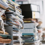 Stacks_of_paperwork_and_files_in_the_office:_work_overload,_files_management_and_administration_concept