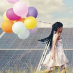 A_funny_girl_carrying_a_colorful_balloon_running_in_a_meadow_with_a_Solar_panel,_photovoltaic._Concept_of_Eco-Friendly_,Clean_Energy_,_Pure_energy_and_Sustainable_energy