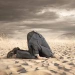 Young_businessman_hiding_head_in_the_sand
