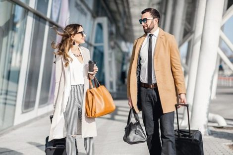 Business_couple_in_coats_walking_out_the_airport_with_luggage_during_the_business_trip