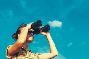 Beautiful_Young_Girl_Looking_Through_Binoculars_On_Blue_Sky_Background._Travel_Holidays_Journey_Concept