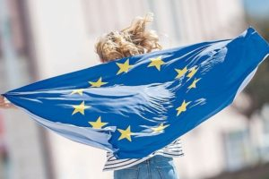 Attractive_happy_young_girl_with_the_flag_of_the_European_Union.