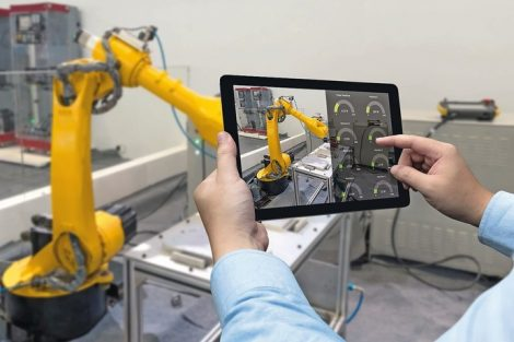 Engineer_hand_using_tablet,_heavy_automation_robot_arm_machine_in_smart_factory_industrial_with_tablet_real_time_monitoring_system_application._Industry_4th_iot_concept.